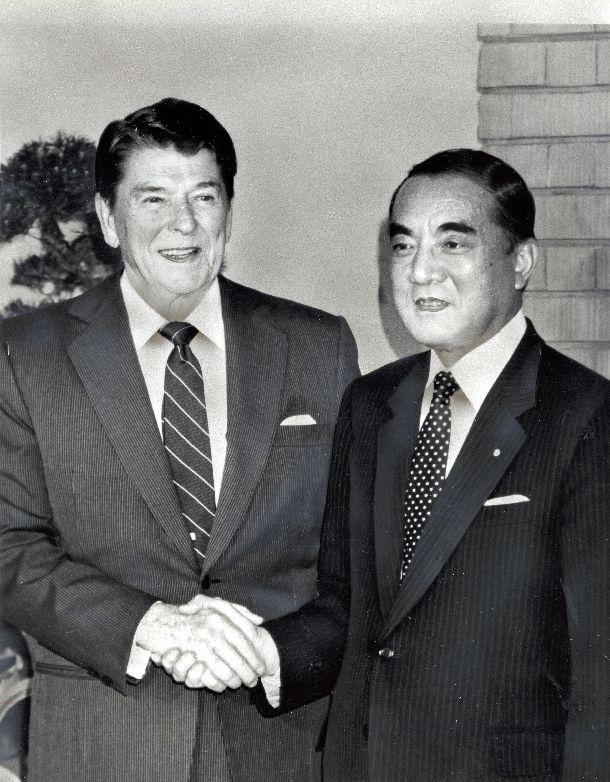 写真・図版 : 1986年5月、首相官邸での日米首脳会談を前に握手するレーガン大統領と中曽根康弘首相=朝日新聞