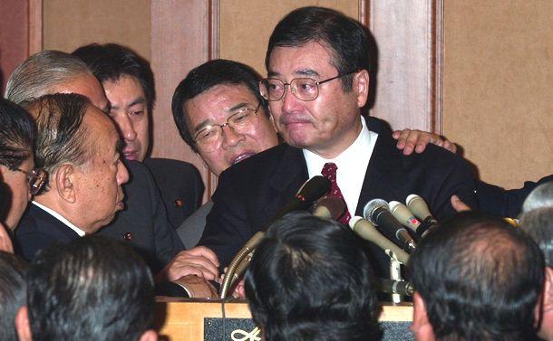 写真・図版 : 森喜朗内閣不信任案に賛成票を投じると発言した加藤紘一自民党元幹事長は、反主流派の合同総会に出席した議員から押しとどめられ、涙を浮かべた=2000年11月20日、東京都港区