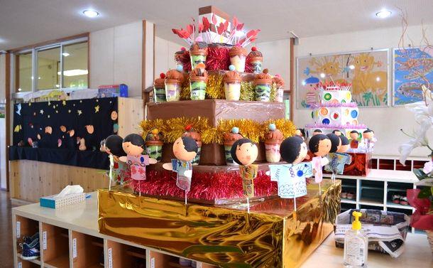 写真・図版 : 桜南幼稚園の玄関に飾られているケーキ。周囲は、園児が囲んでいる