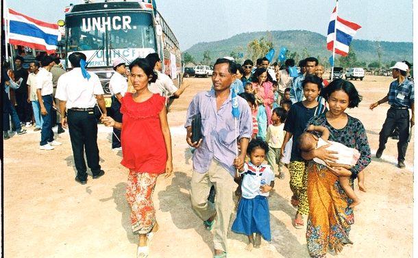 写真・図版 : タイ国境部に避難していたカンボジア難民の帰還がほぼ終了、最後のキャンプ「サイト2」が閉鎖へ。閉鎖式に臨む難民たち。式の終了後、後方のバスでカンボジアへ帰っていく=1993年3月30日