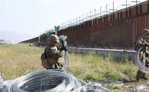 写真・図版 : 移民キャラバンが到着した際、メキシコとの国境検問所のそばの国境の壁の上に鉄条網を設置する米海兵隊員たち=2018年11月20日、サンディエゴ郊外