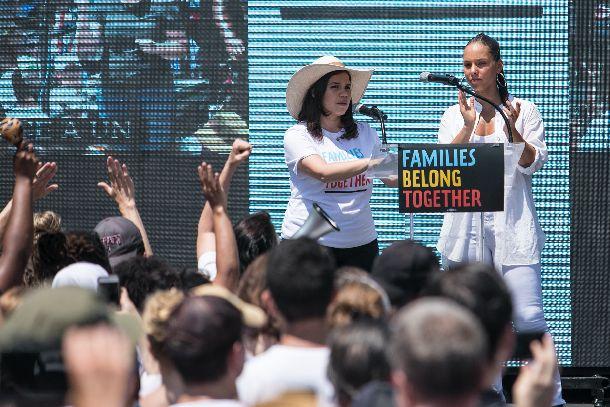 写真・図版 : トランプ政権の移民政策に抗議した移民デモ活動に参加した歌手のアリーシャ・キーズさん(壇上右)と女優のアメリカ・フェレーラさん(同左)=2018年6月30日、ワシントン