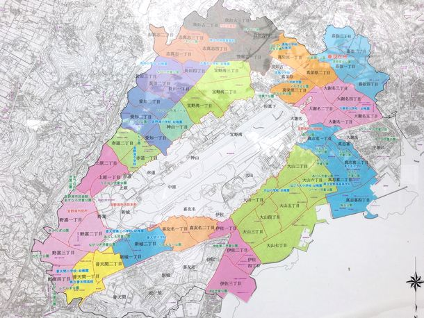写真・図版 : 普天間飛行場が宜野湾市の中心部にあることを示す住宅地図の看板=沖縄県宜野湾市