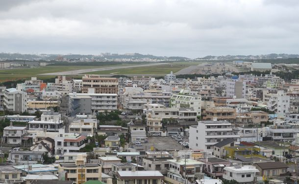 写真・図版 : 住宅に囲まれた中にある米軍海兵隊の普天間飛行場がある宜野湾市の市民は、県民投票で投票権を行使できるのだろうか