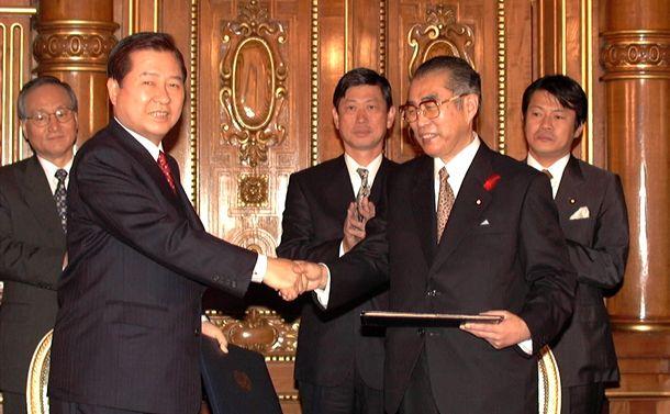 写真・図版 : 日韓共同宣言に署名し、握手する小渕首相(右)と金大中大統領=1998年10月8日、東京・元赤坂の迎賓館で