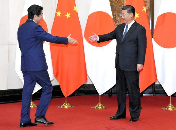 写真・図版 : 会談を前に握手する安倍首相(左)と中国の習近平国家主席=2018年10月26日、北京の釣魚台国賓館