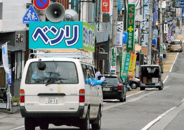 写真・図版 : 2015年統一地方選。新潟県内の5町村議選が告示。旅館や飲食店が立ち並ぶ目抜き通りを、支持を呼びかけながら走る選挙カー=2015年4月21日、JR越後湯沢駅前