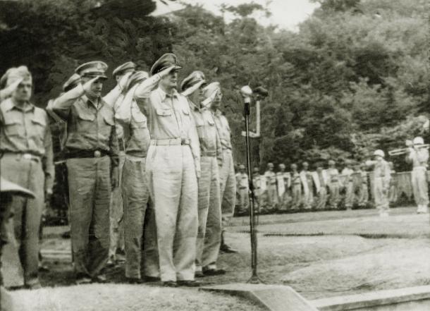 米大使館での国旗掲揚式で、星条旗に敬礼する総司令官のダグラス・マッカーサー元帥