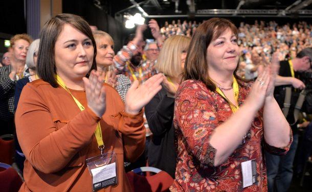 写真・図版 : 英北東部アバディーンで開かれたスコットランド民族党の党大会で、英国からの独立を説くスタージョン氏の演説に拍手を送る支持者たち=2017年3月19日