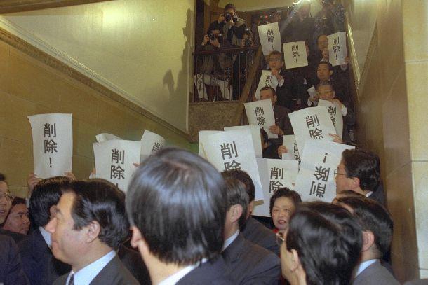 写真・図版 : 住専処理のための予算の削除を求める紙を掲げ、第一委員室前で座り込みを続ける新進党議員(向こう側)=1996年3月5日、国会内で