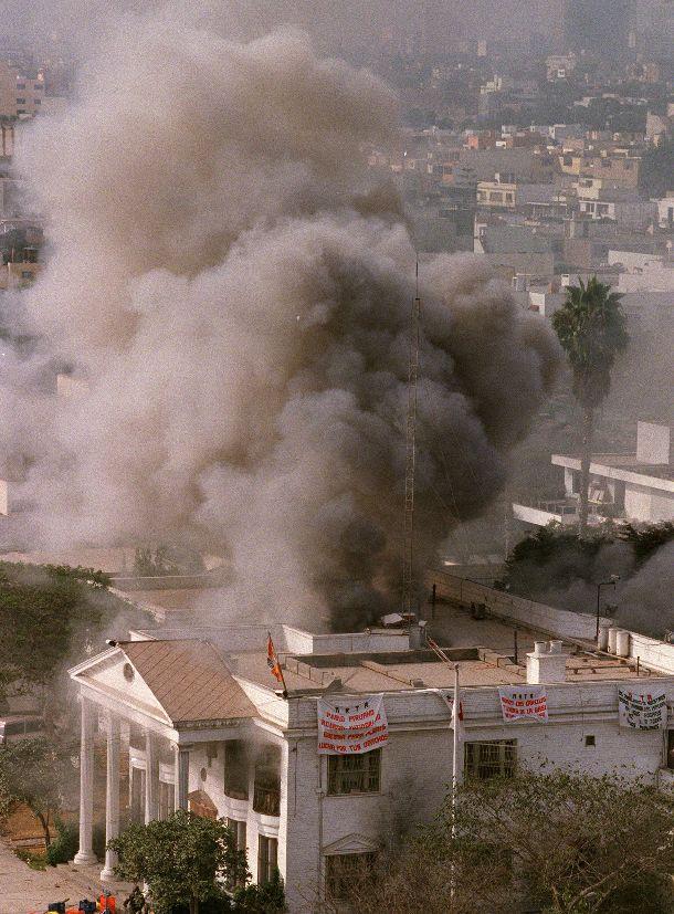 写真・図版 : 人質救出作戦が展開され、黒煙をあげるペルー日本大使公邸=1997年4月22日、リマ市内