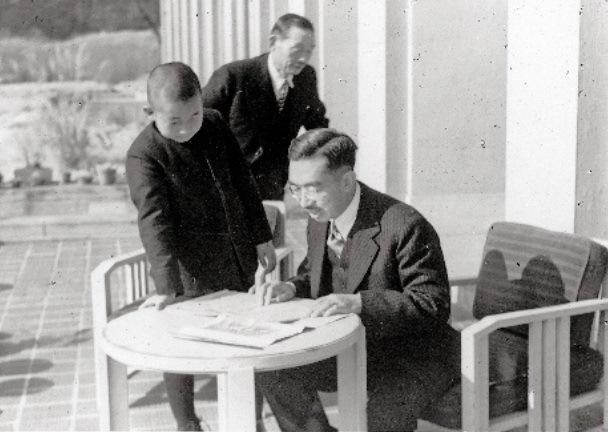 写真・図版 : 進駐軍の新聞「星条旗」を読む昭和天皇と皇太子時代の天皇陛下=1945年12月、一般財団法人日本カメラ財団所蔵