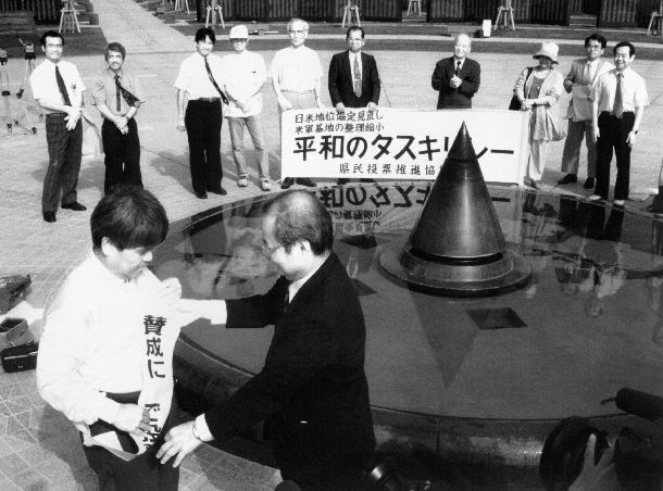 基地整理・縮小、日米地位協定見直しを問で沖縄県民投票。「賛成に○で投票しょう」のたすきをかけた「平和のたすきリレー」の出発式もあった=1996年8月15日、沖縄県糸満市