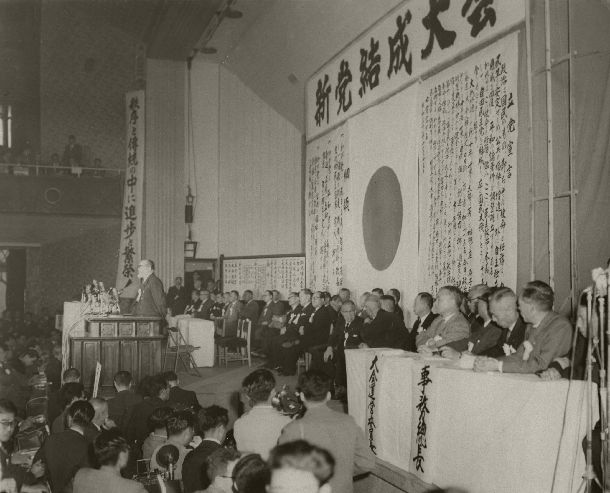 自由民主党の新党結成大会。壇上には鳩山一郎、緒方竹虎、三木武吉、大野伴睦4代行委員、岸信介幹事長らが並び、背景には立党宣言が張られている=1955年11月15日、東京都千代田区神田の中央大学講堂