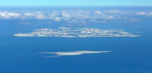 写真・図版 : 北海道・根室半島上空からのぞむ色丹島(奥)。手前は歯舞群島の多楽島(たらくとう)=2018年12月11日