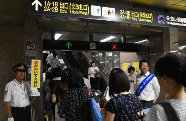 写真・図版 : 駅員が「エスカレーターで歩かないでください」と利用客に呼びかける名古屋市の久屋大通駅=2018年8月