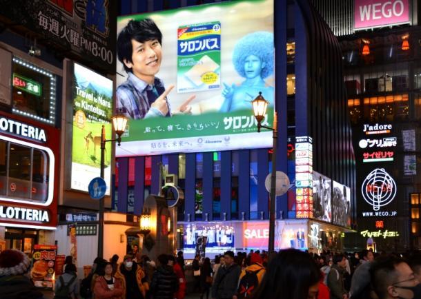 大阪・ミナミの道頓堀に掲げられている二宮和也さんが写った広告。ファンだという女性が写真を撮って橋を渡っていった=2019年1月27日、大阪市中央区