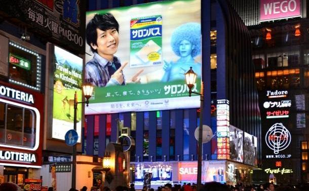 写真・図版 : 大阪・道頓堀に掲げられている嵐の二宮和也さんが写った広告。撮影する女性ファンの姿も