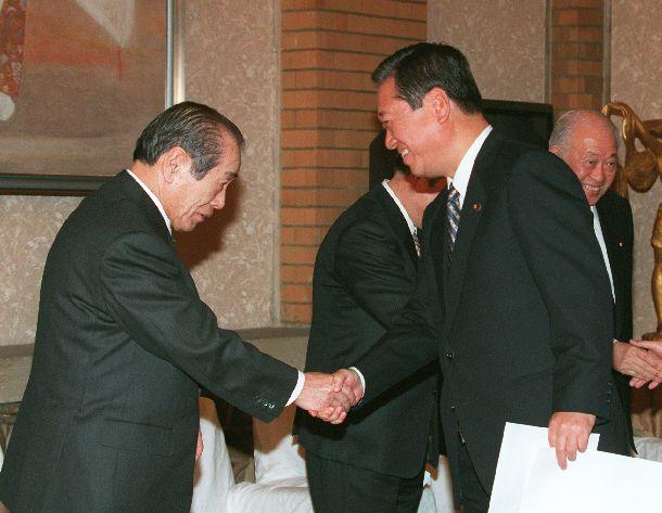 写真・図版 : 自自連立に向けて合意書に署名した後、野中広務官房長官(左端)と握手する小沢一郎自由党党首 =1998年11月19日、首相官邸