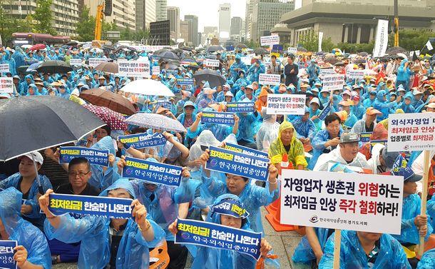 写真・図版 : 豪雨のなか、ソウル中心部で開かれた最低賃金引き上げに抗議する集会=2018年8月29日、東亜日報提供