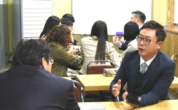写真・図版 : 大手ギョーザチェーン店が開いたフランチャイズ方式の出店説明会で、担当者(右)から熱心に説明を聴く参加者ら=2017年4月19日、ソウル
