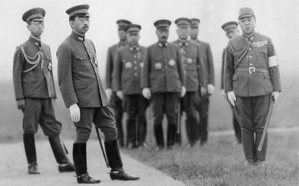 陸軍特別空地連合演習を視察に訪れ、落下傘部隊用の兵装を視察する陸軍軍装の昭和天皇。左は三笠宮さま、正面奥中央は東條英機・首相兼陸相。1942年7月22日