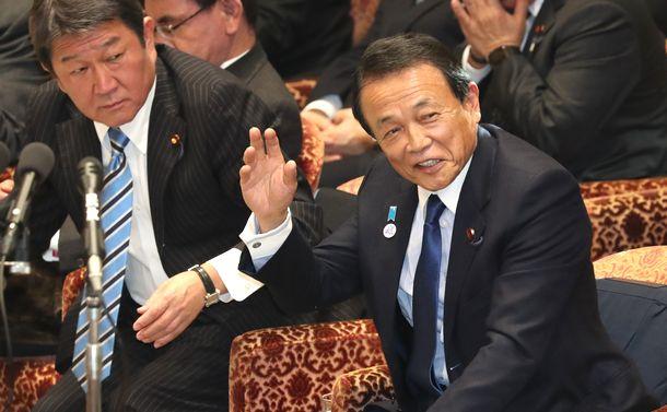 写真・図版 : 衆院予算委で笑いながら挙手する麻生太郎財務相(右)=2019年2月4日