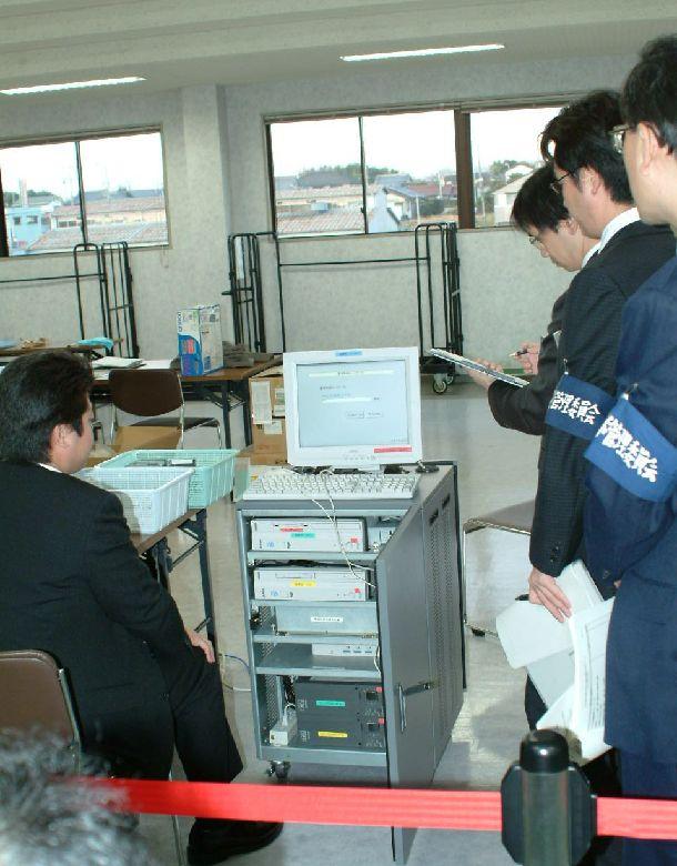 写真・図版 : 可児市市議選でトラブルを起こした電子投票機器を調べる岐阜県選管の職員ら=2003年12月18日、可児市役所