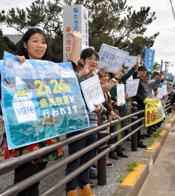 写真・図版 : 宜野湾市役所前の道路を行き交う車に手を振り、県民投票実施を呼びかけた若者ら=2019年1月7日、沖縄県宜野湾市