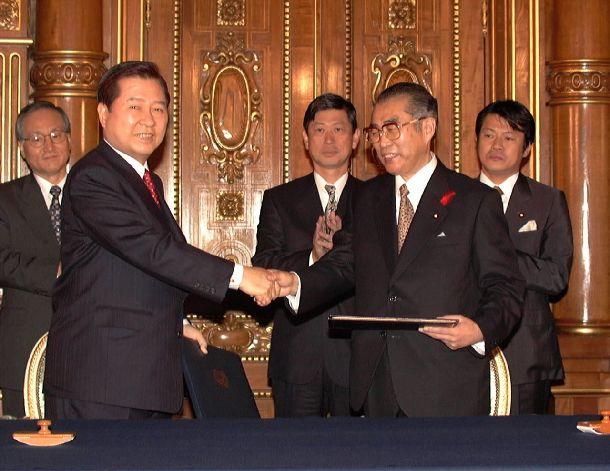 写真・図版 : 日韓共同宣言に署名し、握手する小渕首相(右)と金大中大統領=1998年10月8日、東京・元赤坂の迎賓館