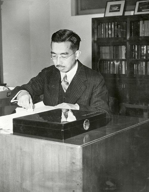写真・図版 : 書斎で公務をする昭和天皇。1946年元旦の新聞紙面用に配信された写真=1945年12月撮影