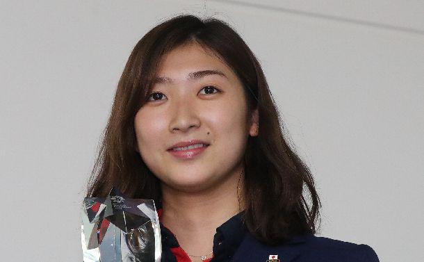 写真・図版 : アジア大会MVPのトロフィーを手に写真撮影に応じる池江璃花子=2018年9月3日、羽田空港