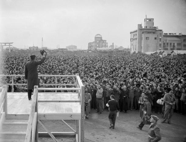 広島市民奉迎式場で市民の歓迎に帽子を振って応える昭和天皇。右奥は元広島産業奨励館(原爆ドーム)