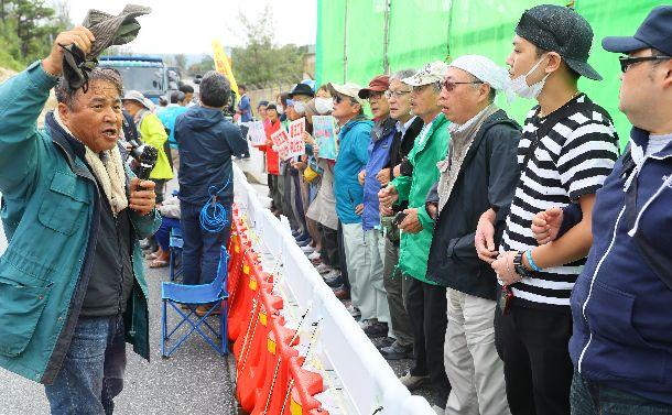 写真・図版 : 沖縄県民投票の翌日、米軍キャンプ・シュワブ前でトラック進入を阻止しようとする人たち=2019年2月25日午前9時26分、沖縄県名護市