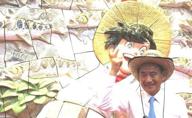 写真・図版 : 釣りキチ三平の大型陶板レリーフの前で麦わら帽子姿で写真撮影に応じる菅義偉官房長官=2016年10月2日、秋田空港
