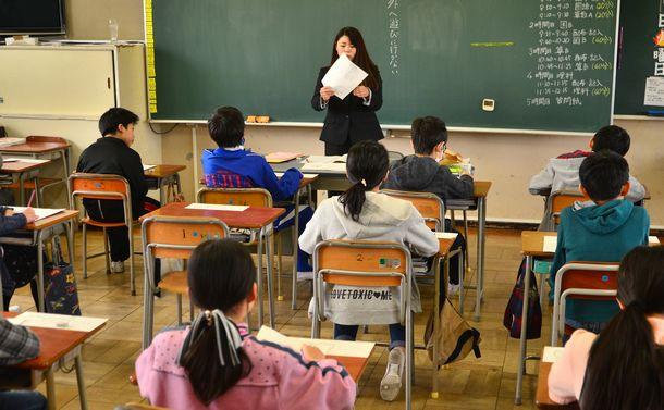 写真・図版 : 全国学力調査の問題が配られ、説明を聞く小学校の児童ら=2018年4月17日、大阪府枚方市