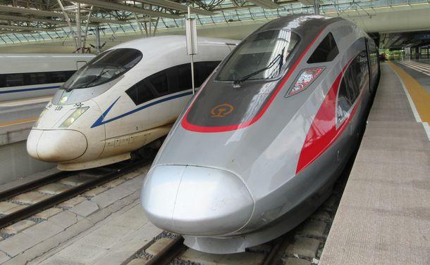 写真・図版 : 中国の高速鉄道復興号(右)と和諧号=2017年7月3日、上海虹橋駅