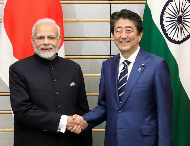 写真・図版 : インドのモディ首相(左)との首脳会談の冒頭、握手を交わす安倍晋三首相=2018年10月29日、首相官邸