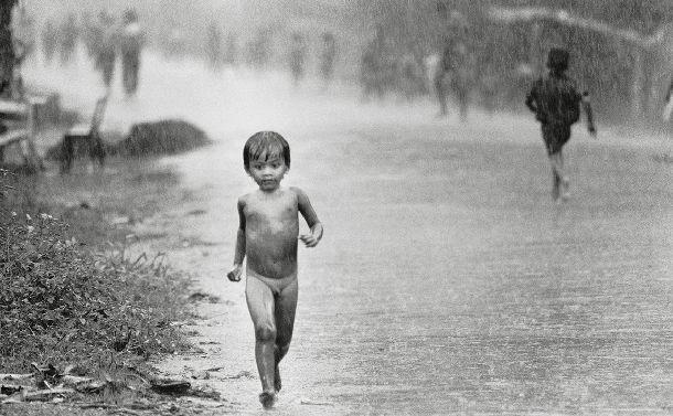 「毎年5月から9月にかけては雨期のため雨が多い。土砂降りのなかを走る子ども(プノンペン、1980年)©Yoshino Oishi