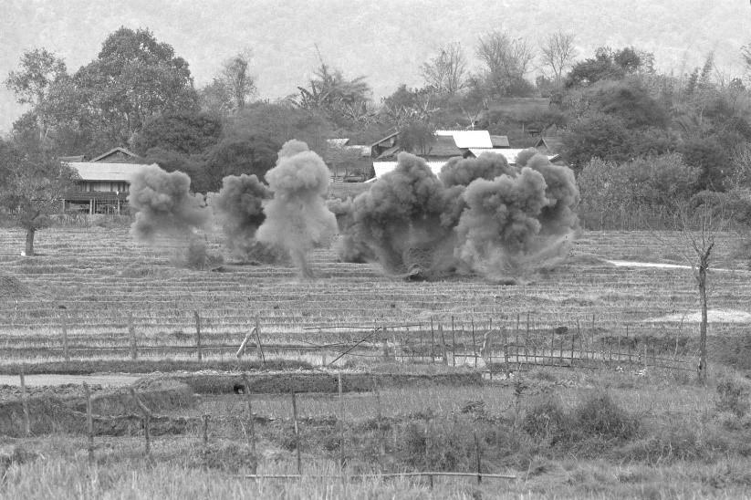 写真・図版 : 集落前の田畑で不発弾処理。UXO Lao(ラオス不発物処理機関)が全土で作業を開始した1994年以降の死傷者は減少している(ラオス・シェンクワン県、2005年)©Yoshino Oishi