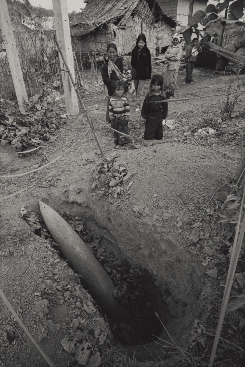 写真・図版 : ウータイ族の集落で1年前にMk82型爆弾が見つかったが、爆発装置の安全弁が外せず放置されたまま(ラオス・サワンナケート県、2005年)©Yoshino Oishi