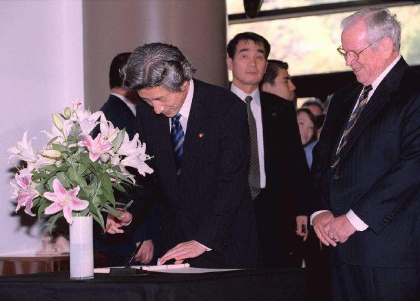 写真・図版 : アメリカでの同時多発テロを受け、弔問のためアメリカ大使館を訪れ記帳する小泉純一郎首相、右はハワード・ベーカー大使=2001年9月17日