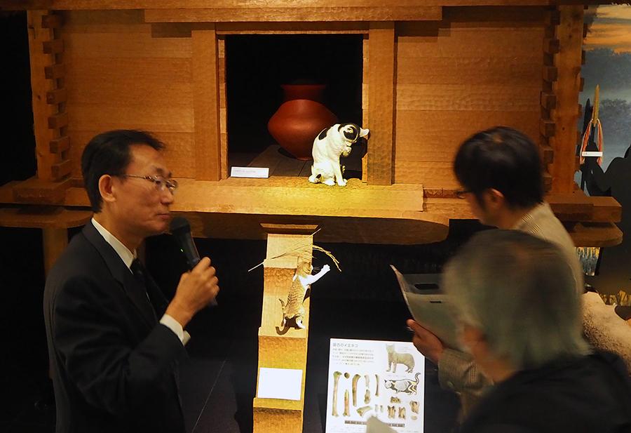 写真・図版 : 解説する藤尾慎一郎教授(左)と、高床倉庫にいる猫の親子=国立歴史民俗博物館