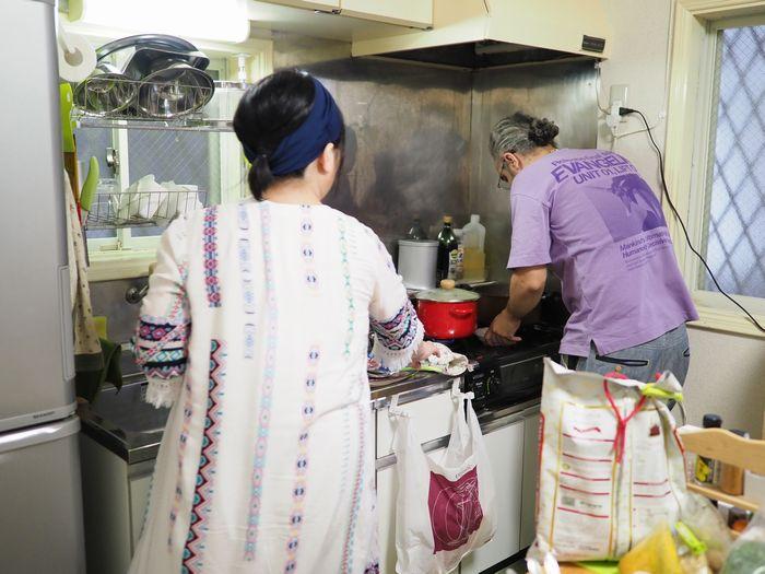 写真・図版 : 手際よく料理するホセさんを、Sさんもアシスト。呼吸もぴったりだ