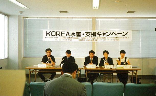 写真・図版 : 新潟港から出港前、北朝鮮の水害支援についての記者会見にのぞむ農協青年部など5団体代表=1996年8月(日本国際ボランティアセンター提供)