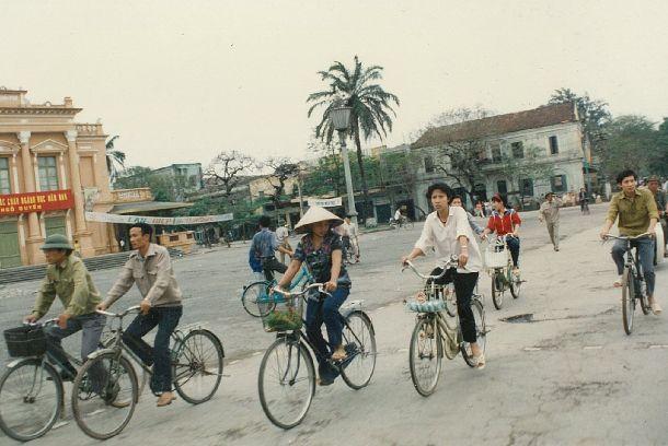 写真・図版 : ベトナム・ハイフォン市中心部の公会堂前を自転車が行き交う=1990年7月(日本国際ボランティアセンター提供)