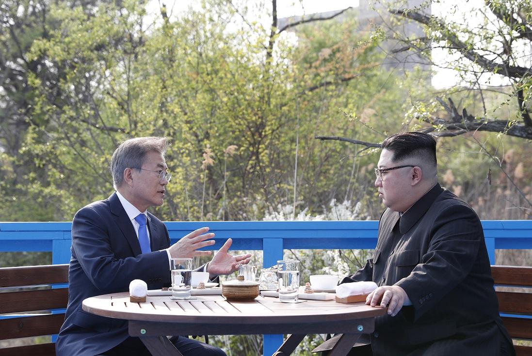 写真・図版 : 板門店で韓国の文在寅大統領(左)と北朝鮮の金正恩委員長(右)は軍事境界線の標識がある「徒歩の橋」まで散歩をし、ベンチに座って2人で話し込んだ=2018年4月27日、韓国共同写真記者団撮影