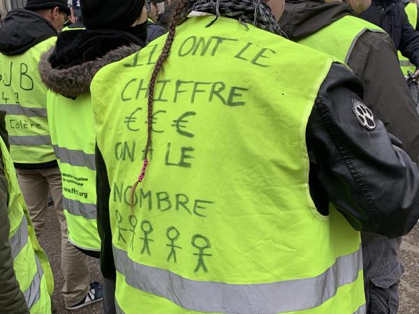 アンジェのデモで、ベストには「あいつらには数(カネ)がある。俺たちには数(仲間)がいる」と書いてあった。