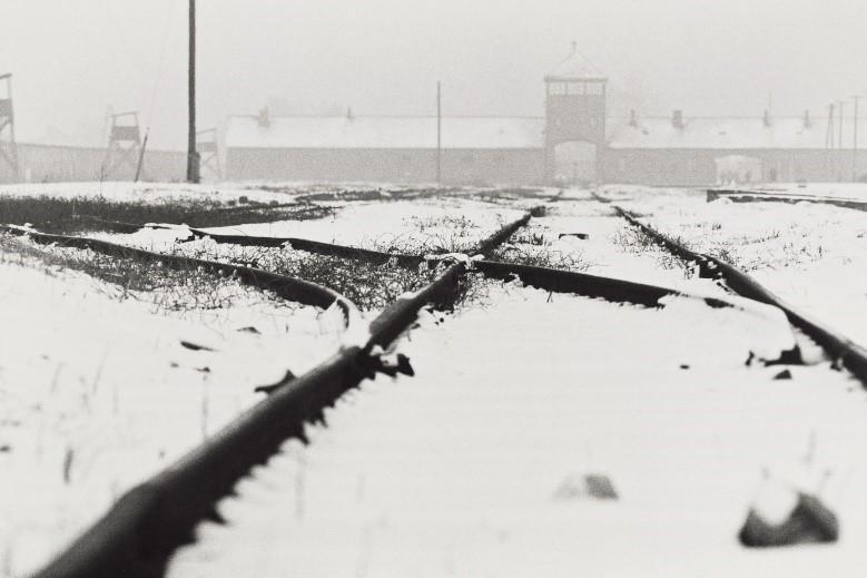 写真・図版 : 強制収容所の「死の門」と呼ばれたSS(ナチス親衛隊)の中央衛兵所が前方正面に見える(アウシュヴィッツ ビルケナウ、1987年)©Yoshino Oishi