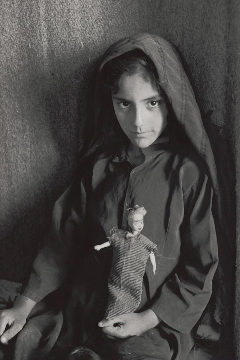 パグリ(9)は「人形の服、わたしが作ったの。学校に通えるようになってうれしい」と微笑む(アフガニスタン・カブール、2002年)©Yoshino Oishi
